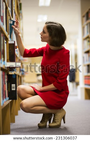 Young woman in library found book for reading - stock photo