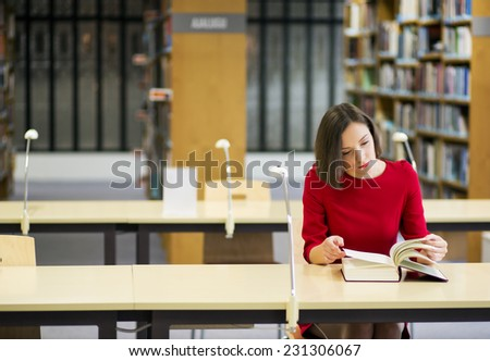 Young woman in library seek knowledge from book - stock photo