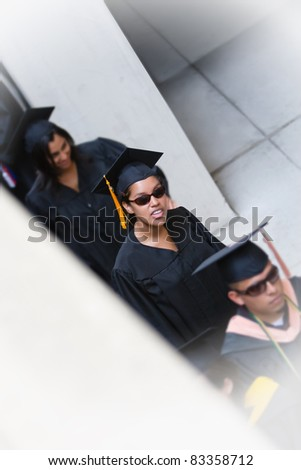 Young woman in line to graduate wearing sunglasses - stock photo