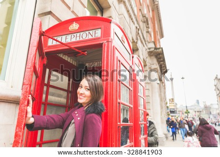 Young woman in London in front of a typical red phone booth. She is standing on the entrance, holding the door with her hand, smiling and looking at camera. Tourism and lifestyle concept - stock photo