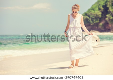 Young woman in long white dress with hat in her hand walks along tropical beach having great summer time on holidays. Summer vacation, holidays, serenity, travel, lifestyle concept  - stock photo