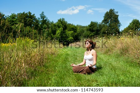 Young woman in lotus position meditating in nature - stock photo