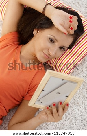 Young woman in love, looking at photo of boyfriend, daydreaming at home. - stock photo