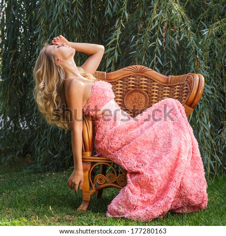 Young woman in luxurious pink dress sitting on chair outdoor portrait - stock photo