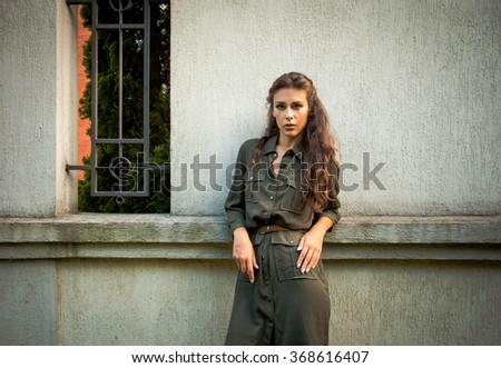 young woman in military style fashion dress lean on wall, day shot, natural light  - stock photo