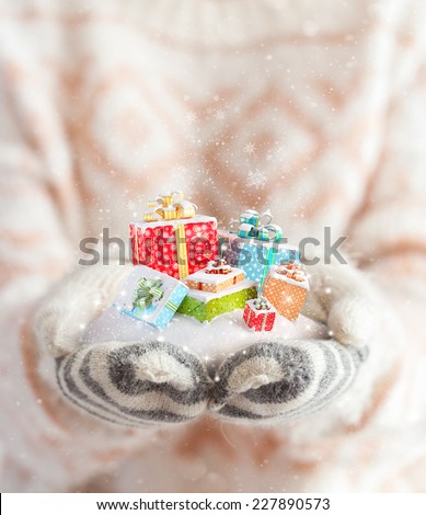 Young woman in mittens holding snow in her hands with gift boxes. Unusual christmas concept - stock photo