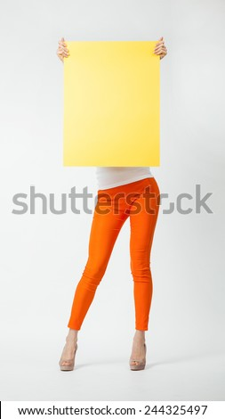 Young woman in orange pants holding blank yellow placard hiding behind it, full length portrait on neutral background - stock photo