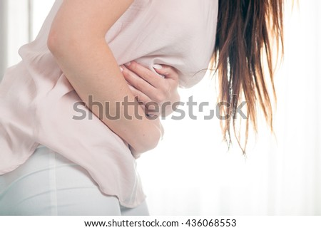 Young woman in pain holding her stomach, casual style indoor shoot - stock photo