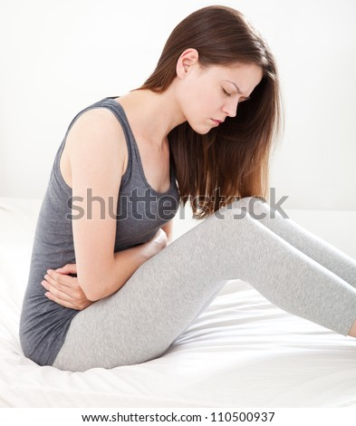 Young woman in pain sitting on bed, on white background - stock photo