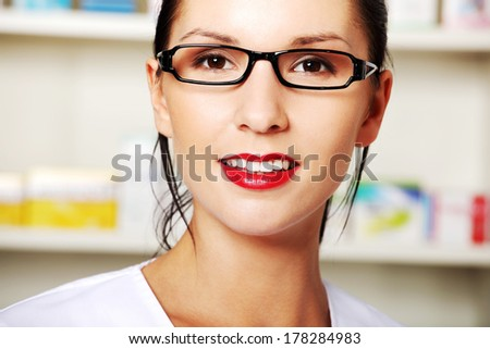 Young woman in pharmacist uniform standing in drugstore  - stock photo