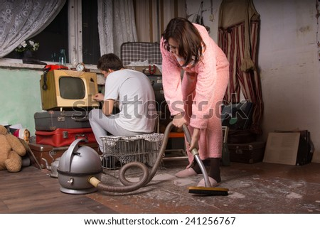 Young Woman in Pink Bathrobe Cleaning a Messy Abandoned Room Using Vacuum While Partner is Busy with Unused Items at the Back. - stock photo