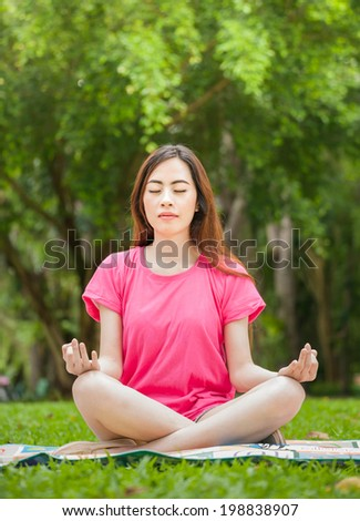 Young woman in pink sitting on grass and practicing yoga - stock photo