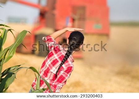 Young woman in plaid shirt standing in wheat field and looking at combine during harvest - stock photo