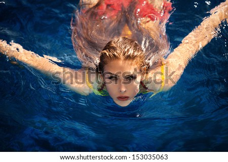 young woman in pool swimming looking at camera shot from above - stock photo