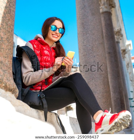 Young woman in red clothes using smart phone in the old city center. Traveling application concept - stock photo