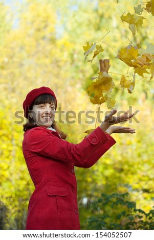 Young woman in red coat throwing yellow maple leaves in autumn - stock photo