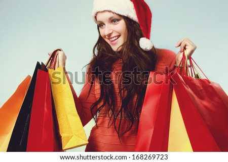 Young woman in red dress and santa helper hat with shopping bags - stock photo