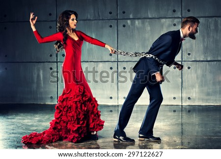 Young woman in red dress holding man on heavy chain. He tries to escape. Elegant evening clothing. - stock photo