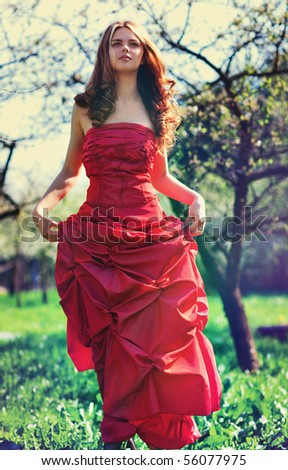 Young woman in red dress in garden. Film style colors. - stock photo