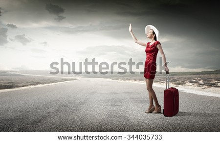 Young woman in red dress on road with red luggage - stock photo