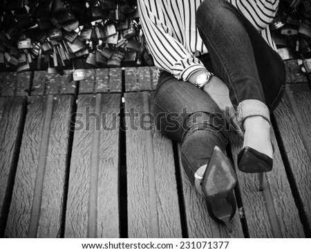 Young woman in red high heel shoes sitting on Love locks bridge in Paris. Retro aged photo. Black and white. Shadowed angles. - stock photo