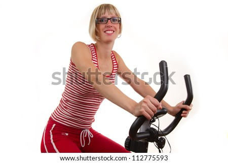 Young woman in red on exercise bike - stock photo
