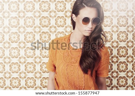 Young woman in 1970's fashion looking down - stock photo