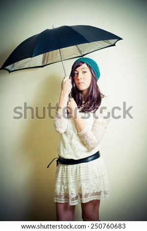 Young woman in 70s hippie style posing with umbrella vintage color effect - stock photo