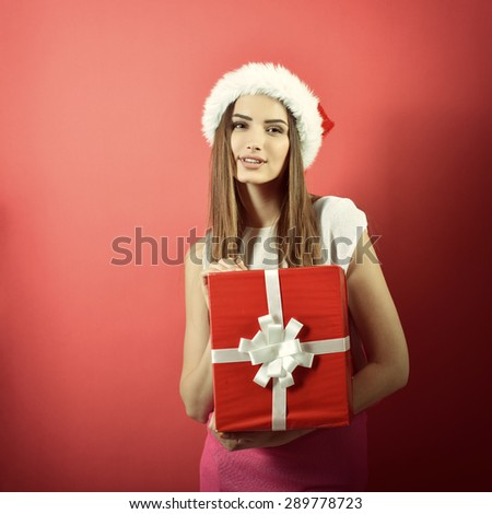 Young woman in santa helper hat with gift box and shopping bag over red background. Christmas, x-mas, winter, sale concept. - stock photo