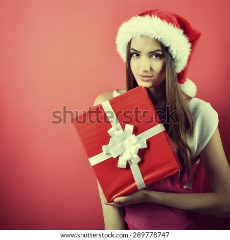 Young woman in santa helper hat with gift box over red background. Christmas, x-mas, winter, sale concept, image toned - stock photo