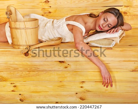 Young woman in sauna. Overheating danger. - stock photo