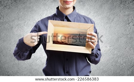 Young woman in shirt with wooden frame in hands - stock photo