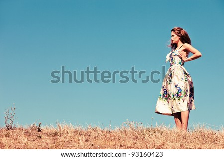 young woman in silk dress stand on hill in dry grass with clear blue sky in background, grain added - stock photo