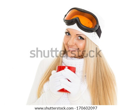 Young woman  in ski glasses  and  winter warm clothes  with red cup stands on a white background. Winter sports. - stock photo