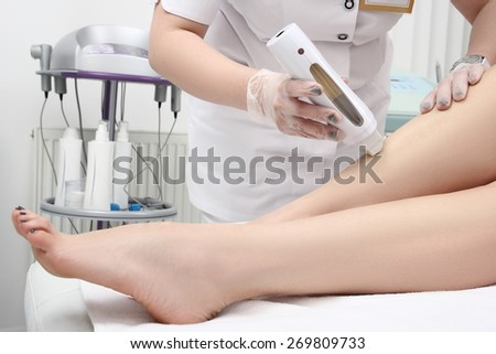 Young woman in Spa getting legs waxed for hair removal - stock photo