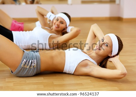 Young woman in sport wear doing sport in gym - stock photo