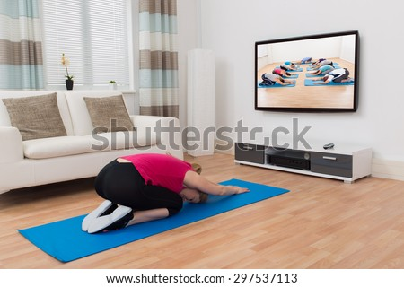 Young Woman In Sportswear Doing Yoga In Front Of Television At Home - stock photo