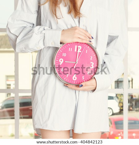 Young woman in striped shirt holding red alarm clock feeling pain or hunger in stomach - stock photo