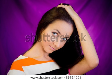 Young woman in studio against purple background - stock photo