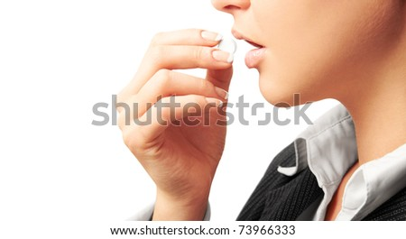 Young woman in suit taking white pill. Isolated on white. Closeup. - stock photo
