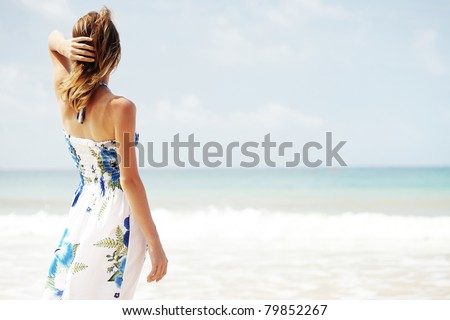 Young woman in summer dress standing by blue sea and looking to horizon - stock photo
