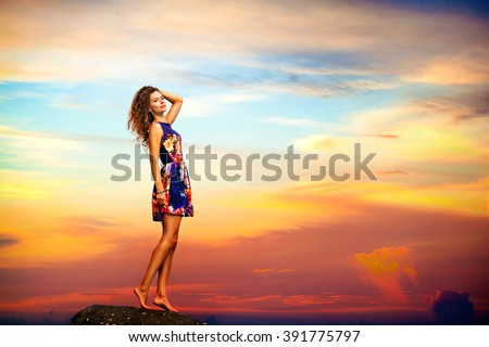 Young woman in summer dress standing on a rock - stock photo