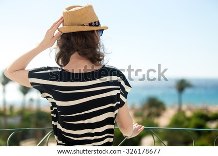 Young woman in summer dress standing on balcony with sea view, enjoying beautiful tropical scenery, looking at seashore, holding her straw hat from breeze, back view - stock photo