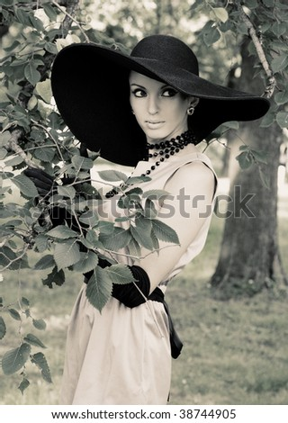 Young woman in summer park. Retro style. - stock photo