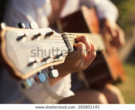Young woman in sun park holding a guitar and playing music - stock photo
