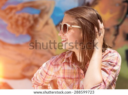 young woman in sunglasses behind graffiti wall - stock photo