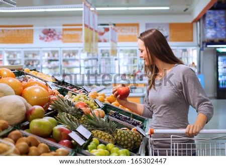 young woman in supermarket choosing fruits - stock photo