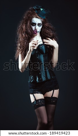 Young woman in the image of a sad gothic freak clown smelling withered flower - stock photo