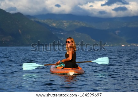Young woman in the kayak at mountain lake - stock photo