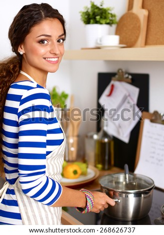 Young woman in the kitchen preparing a food - stock photo